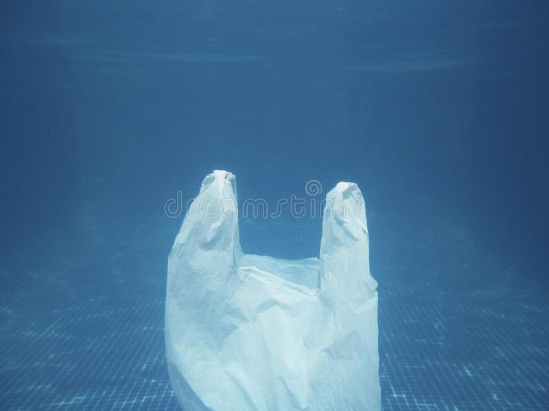 Plastic bag floating into the water. Polluted enviromental. Recycle. Garbage stock photography