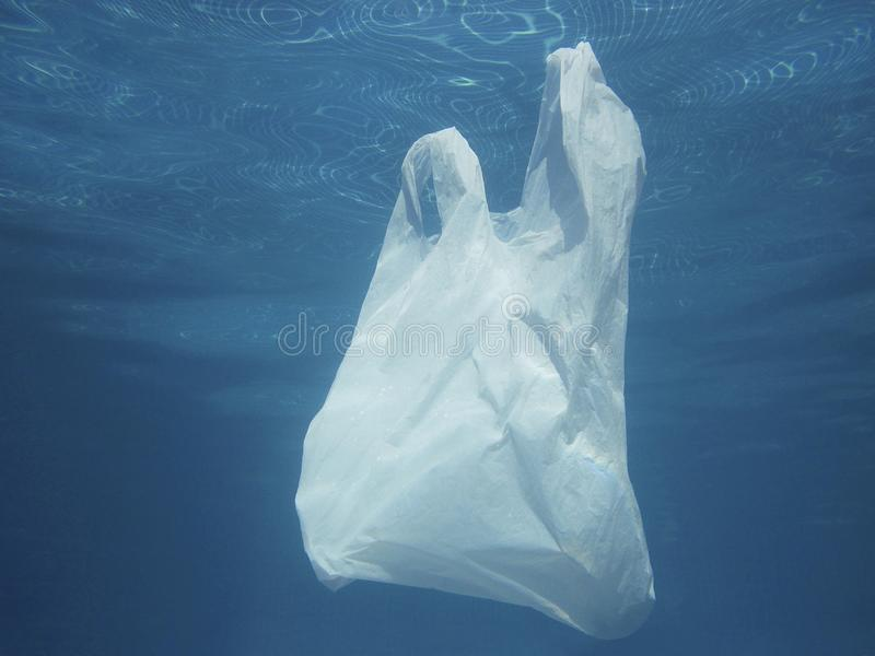 Plastic bag floating into the water. Polluted enviromental. Recycling. Plastic bag floating into the water. Polluted enviromental. Recycle garbage royalty free stock images