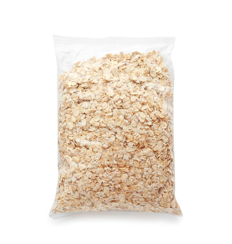 Plastic bag with raw oatmeal flakes on white background stock photo