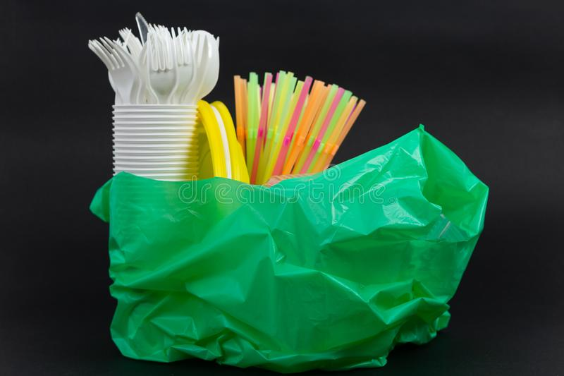 Plastic bag with single use straws plates and cutlery waste royalty free stock images
