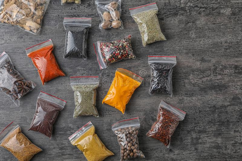 Plastic bags with different spices on grey background stock image