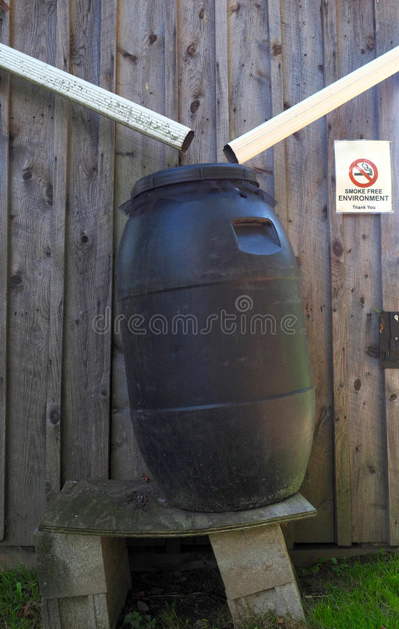 Plastic Barrel for Collecting Rain Water. Pipes and large plastic barrel used for collecting and storing rain water royalty free stock photos
