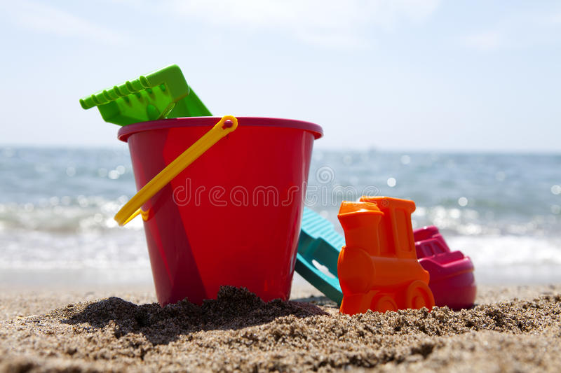 Plastic beach toys. Plastic toys at the beach against blue sky and ocean stock images