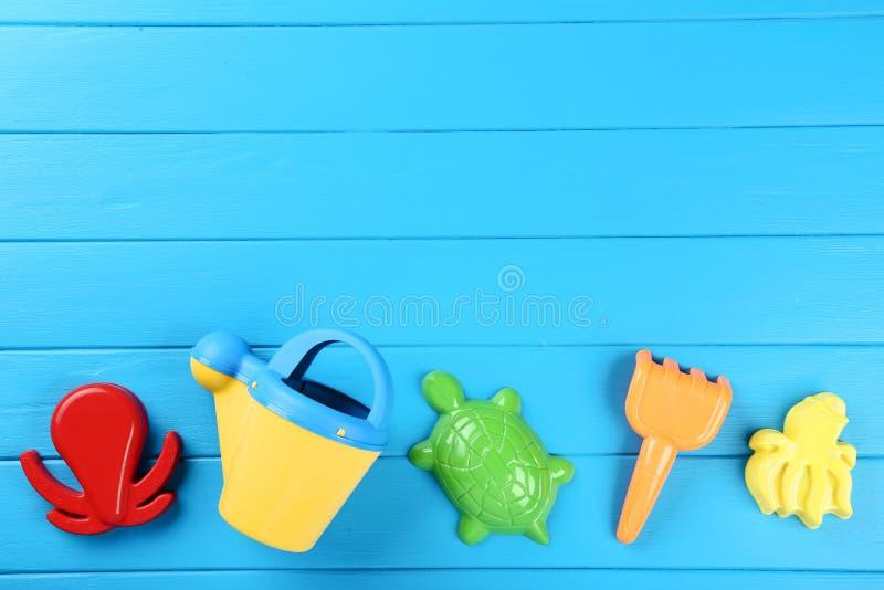 Plastic beach toys. On blue wooden table stock photos