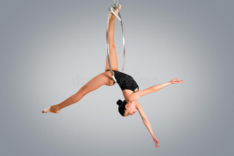 Plastic beautiful girl gymnast on acrobatic circus ring in flesh-colored suit. Aerial ring royalty free stock image