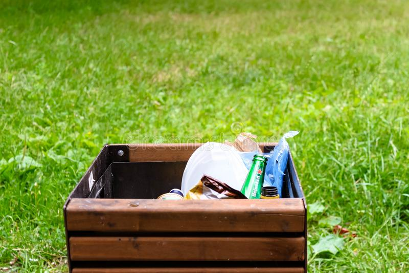 Plastic beschikbaar afvalclose-up in de overbelaste bak van het afvaldienblad op gras achtergrondverontreinigingsconcept stock afbeelding