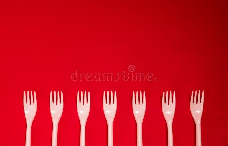 Plastic beschikbare vorkenwerktuigen op een rode achtergrond stock afbeeldingen