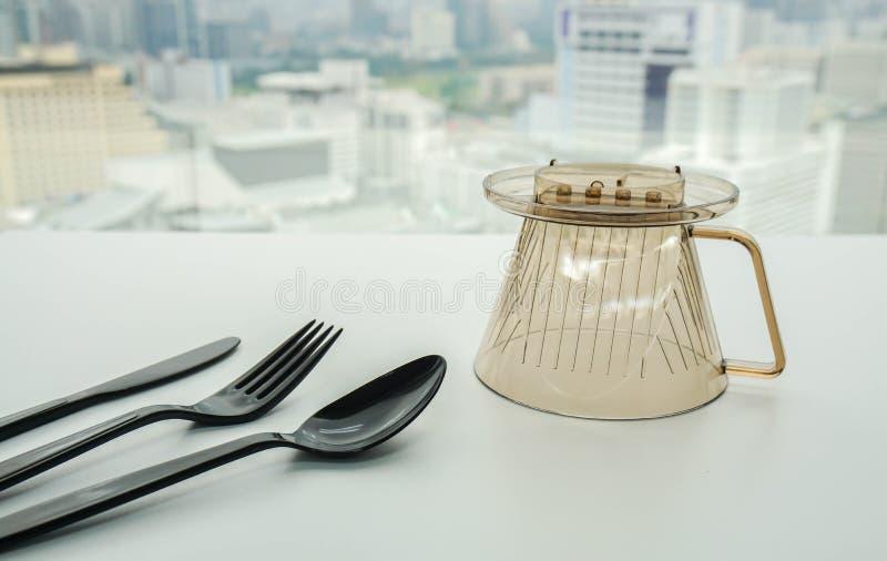 Plastic bestekwerktuigen met de creatieve mok van het ontwerpwater op eettafel stock fotografie