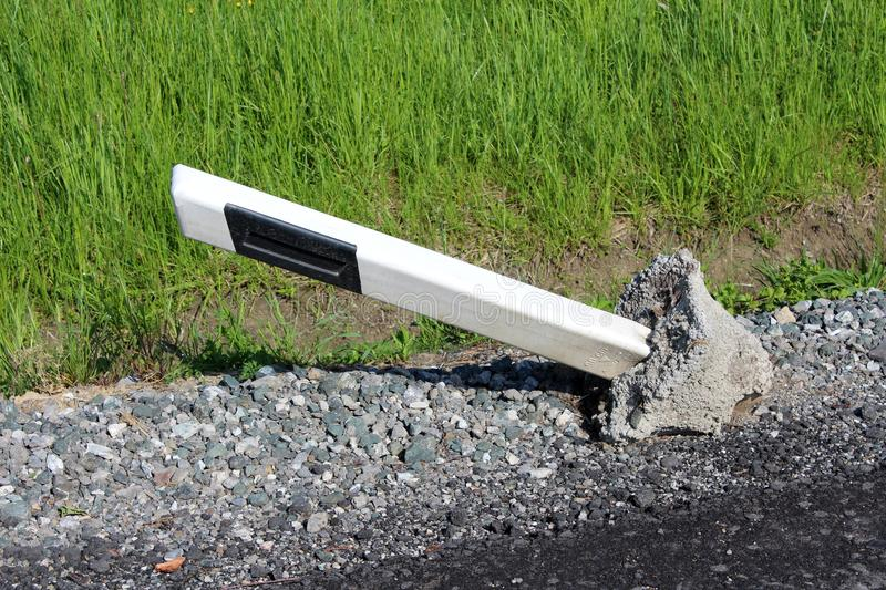 Plastic black and white roadside pole with concrete foundation knocked out of its position stock photos