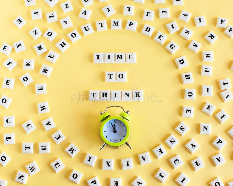 Plastic block cube with word TIME TO THINK and around scattered individual letters and alarm clock on yellow background. stock photography