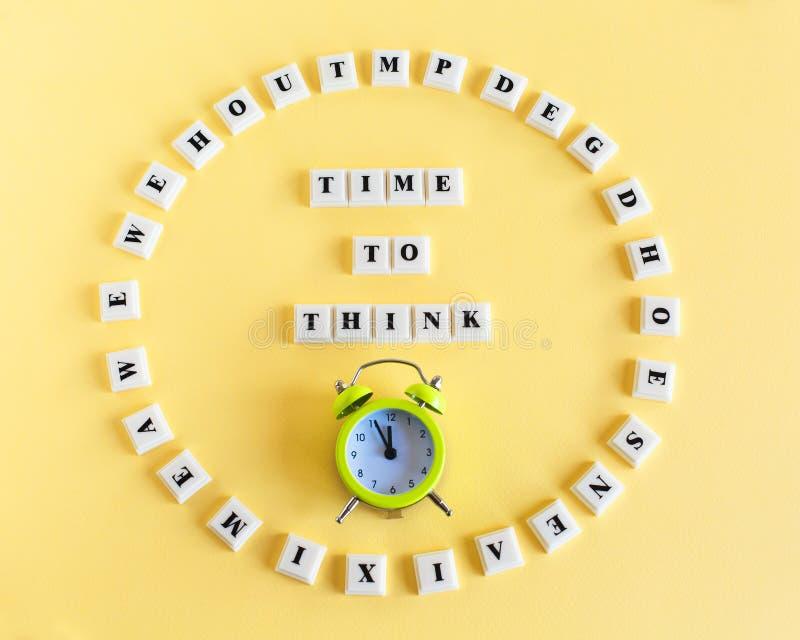 Plastic blokkubus met woordtijd TE DENKEN en wekker op gele achtergrond stock fotografie