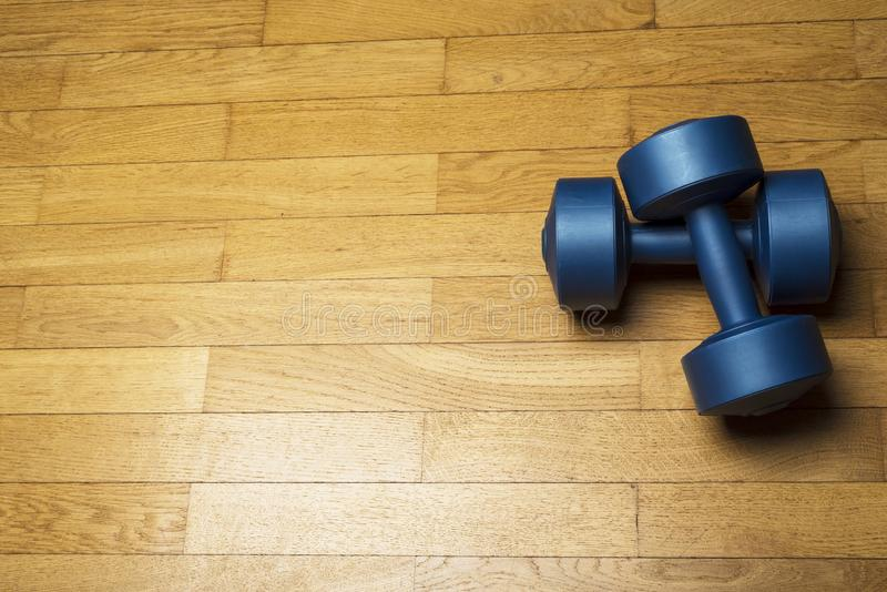 Plastic blue dumbbells on wooden, brown floor royalty free stock images