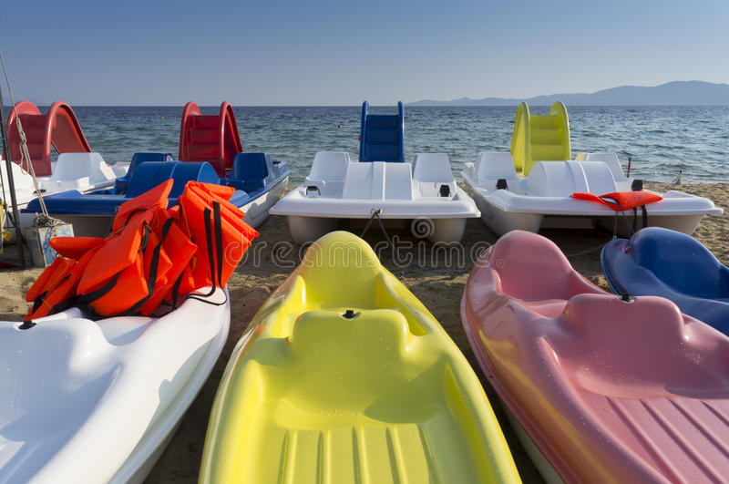 Plastic boats in different colors. Plastic boats in different colours, with life vests on them, near by the seashore stock image