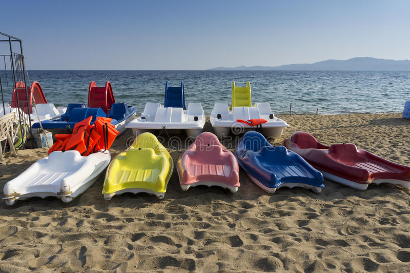 Plastic boats in different colours. With life vests on them, near by the seashore royalty free stock photo