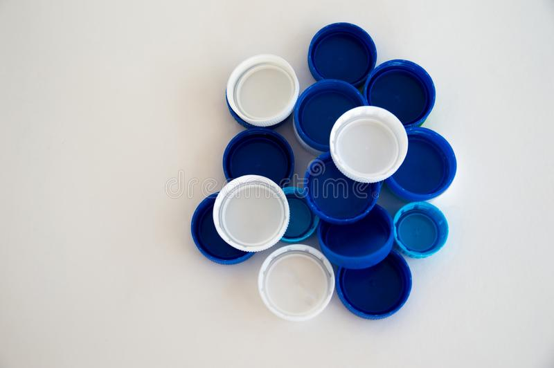 Plastic bottle caps and drinks are on a white background. Isolate plastic trash for recycling. Polymers in human life royalty free stock images