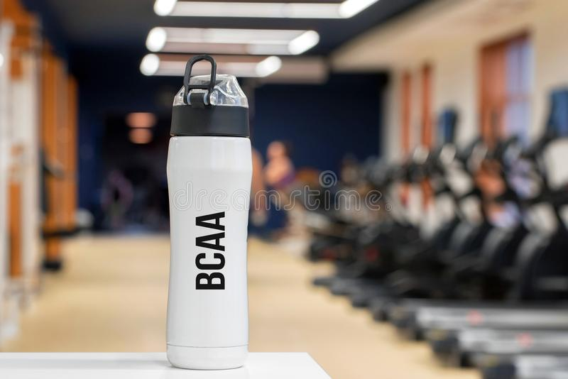 Plastic bottle or cup with Branched-chain amino acid drink close up. White fitness bottle with branched-chain amino acid and blurred background with people stock photography