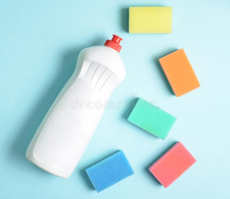 Plastic bottle of dishwashing detergent, sponges on blue pastel background, top view, flat lay, minimalism. Plastic bottle of dishwashing detergent, sponges on stock photography