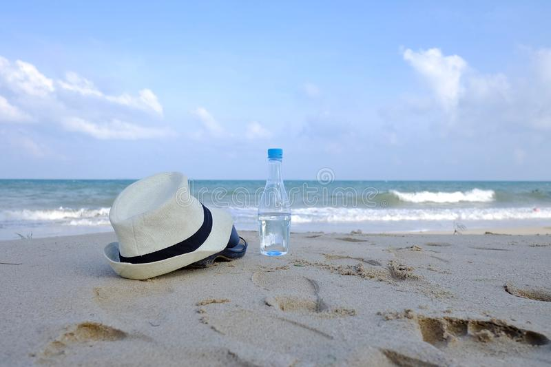 A plastic bottle of drinking water littering on the clean beach. Sea view with an environmental cleaning concept royalty free stock image