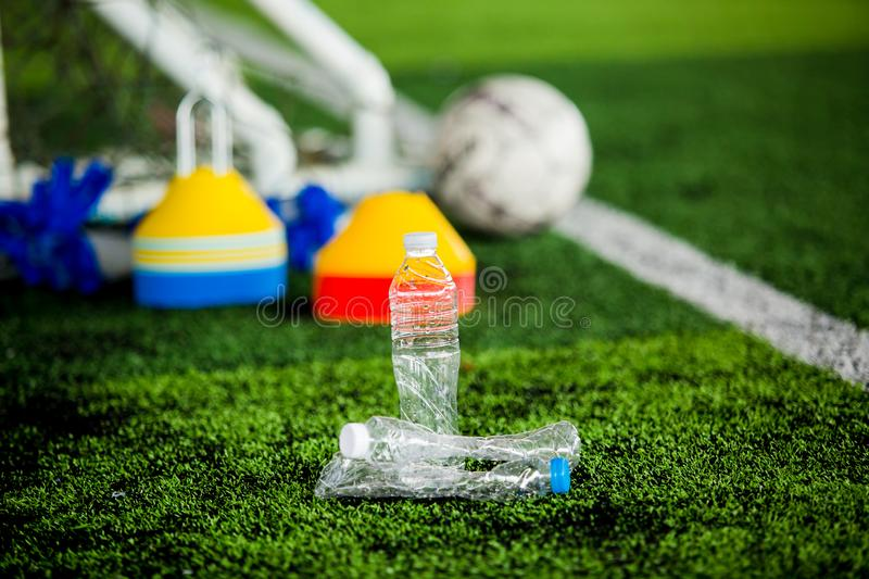 Plastic bottle on a football field with blurry soccer training Equipment on Artificial turf. It is waste from football match royalty free stock photo