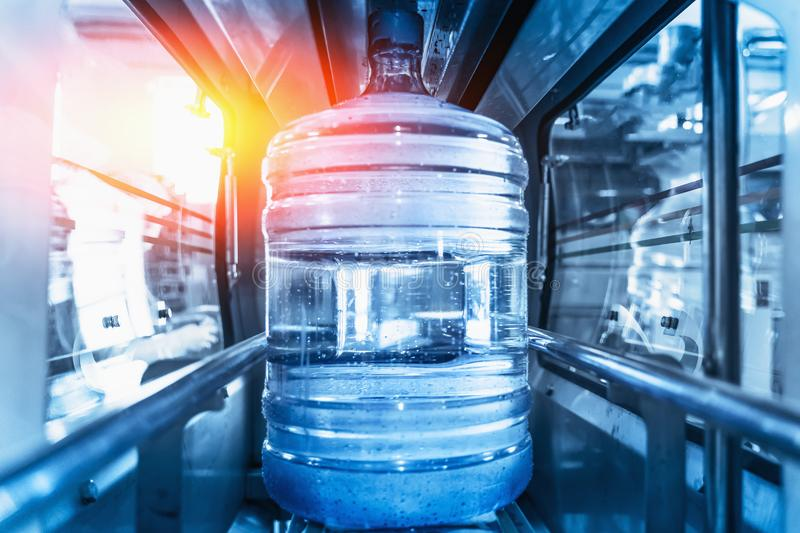 Plastic bottle or gallon of purified drinking water inside automated conveyor production line. Water factory, blue toned stock photography