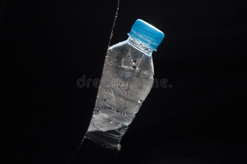 Plastic bottle hanging for drinking to quench thirst. Plastic bottle hanging for drinking to quench thirst on black background royalty free stock image