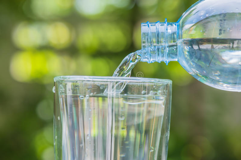 plastic bottle pouring water into a glass on green blurry background royalty free stock images