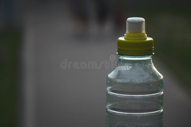Plastic bottle top full with water with yellow cap in a park or garden with green trees in blurred background Recyclable beverage. Container that protects the royalty free stock photos
