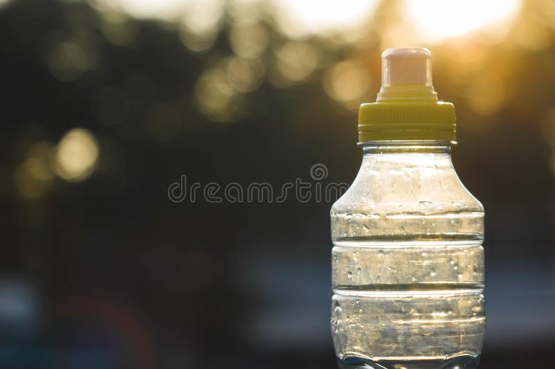 Plastic bottle top full with water with yellow cap in a park or garden with green trees in blurred background Recyclable beverage. Container that protects the royalty free stock photography