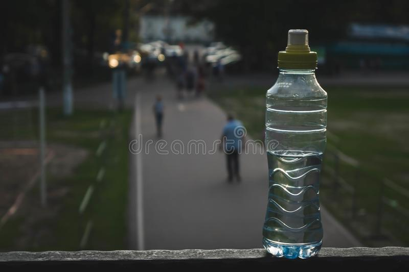 Plastic bottle top full with water with yellow cap in a park or garden with green trees in blurred background Recyclable beverage. Container that protects the royalty free stock images