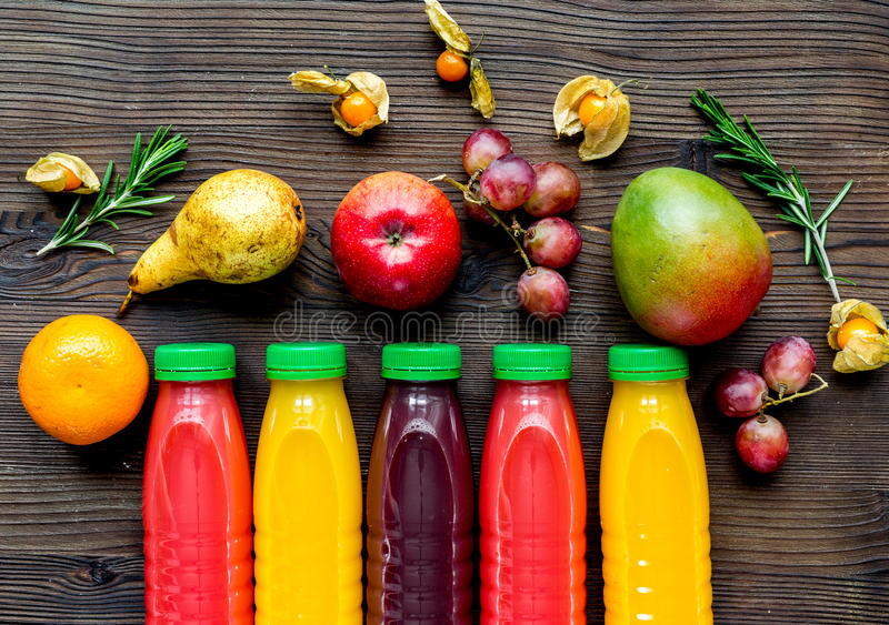 Plastic bottles with fruit drinks on wooden background top view. Colorful plastic bottles with fruit fresh drinks on wooden table background top view stock photography