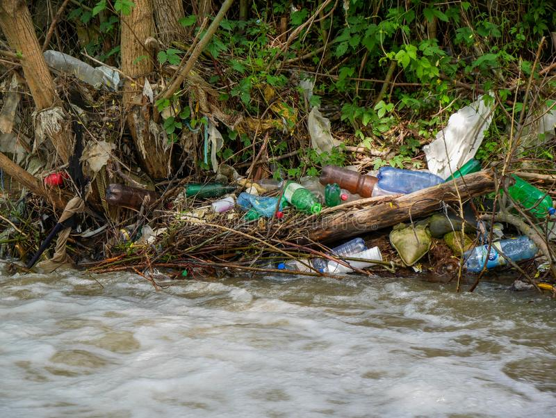 Plastic bottles and human trash in the river, conceptual human negligence image. Bancu, Romania- 20 May 2019: Plastic bottles and human trash in the river royalty free stock photography