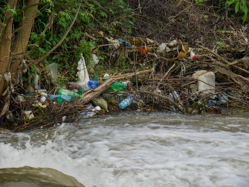 Plastic bottles and human trash in the river, conceptual human negligence image. Bancu, Romania- 20 May 2019: Plastic bottles and human trash in the river royalty free stock photos