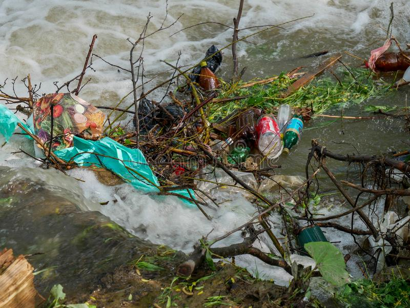 Plastic bottles and human trash in the river, conceptual human negligence image. Bancu, Romania- 20 May 2019: Plastic bottles and human trash in the river stock photography