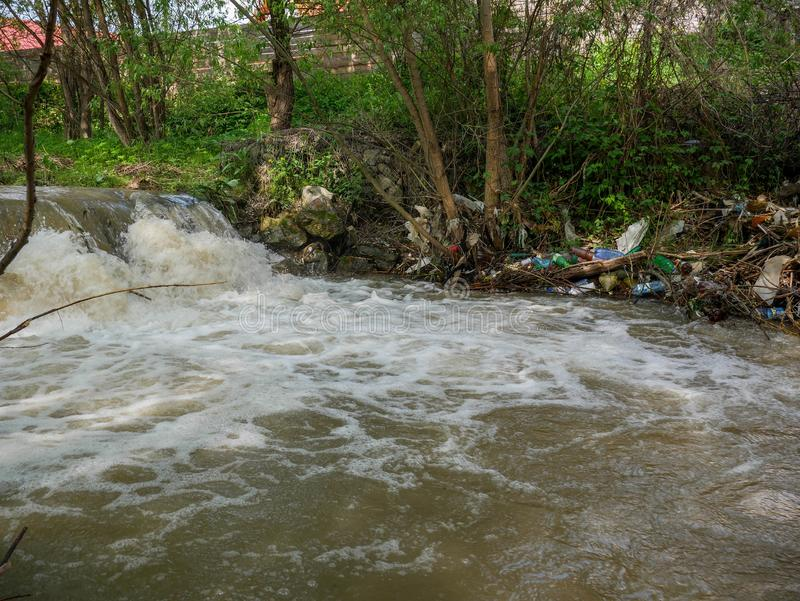 Plastic bottles and human trash in the river, conceptual human negligence image. Bancu, Romania- 20 May 2019: Plastic bottles and human trash in the river stock image