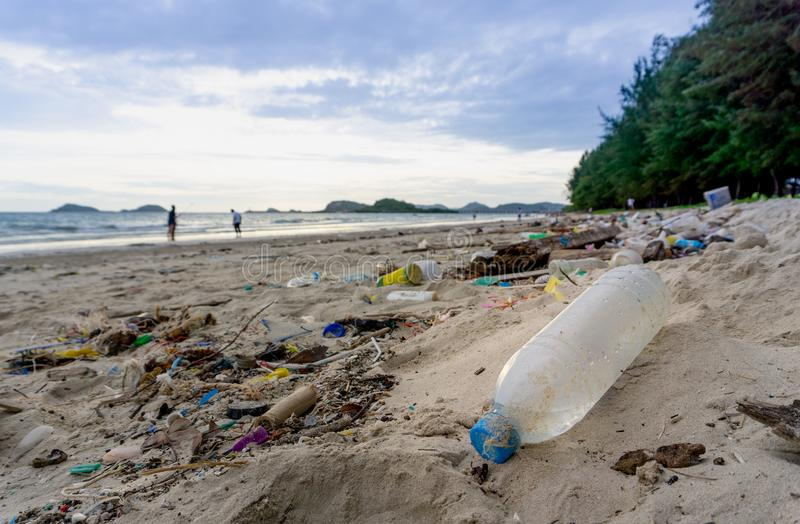 Plastic bottles left on the dirty sand beach with various garbages royalty free stock photo