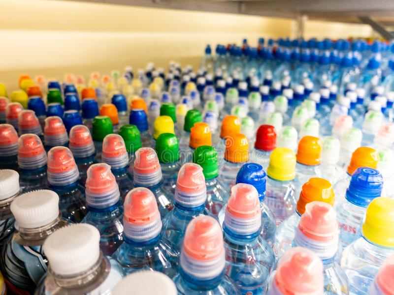 Plastic bottles with mineral water. Closeup on water bottles in raw and lines. Plastic bottles, colorful caps. Plastic bottles wit stock photos