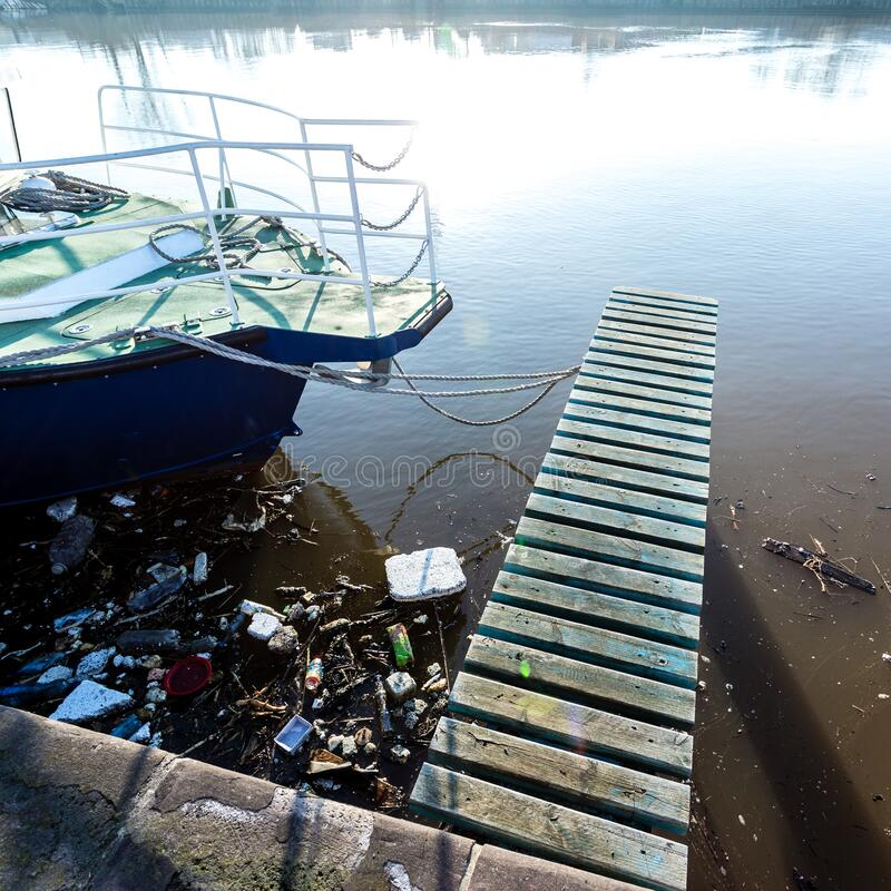 Free Plastic Bottles, Packages, Trash In River Near Yacht. Illegal Garbage Dump, Water Pollution Royalty Free Stock Photos - 189211548