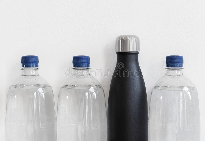 Plastic bottles with reusable bottle made from stainless steel. Plastic free alternative concept, with copy space royalty free stock images