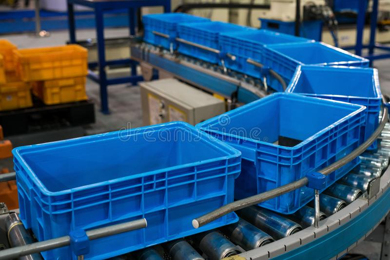 Plastic box on roller line for tranfer production part in prodine lin in factory. Production, transportation concept royalty free stock photo