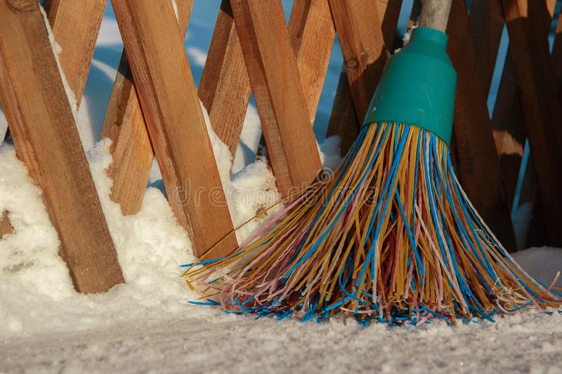 A plastic broom with multicolored bristles of the pile stands in the snow. The concept of cleaning the area of snow in the winter royalty free stock image