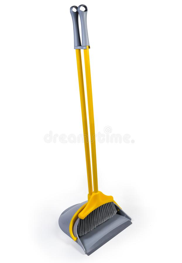 Plastic broom for sweeping floors with dustpan on white background. Kit of the yellow plastic broom with gray bristles for sweeping floors and long-handled royalty free stock image
