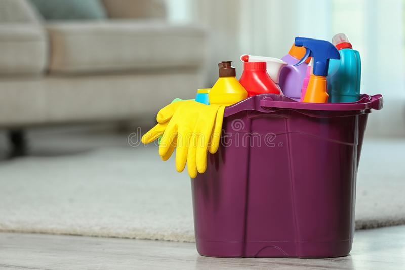Plastic bucket with different cleaning products on floor indoors stock photos