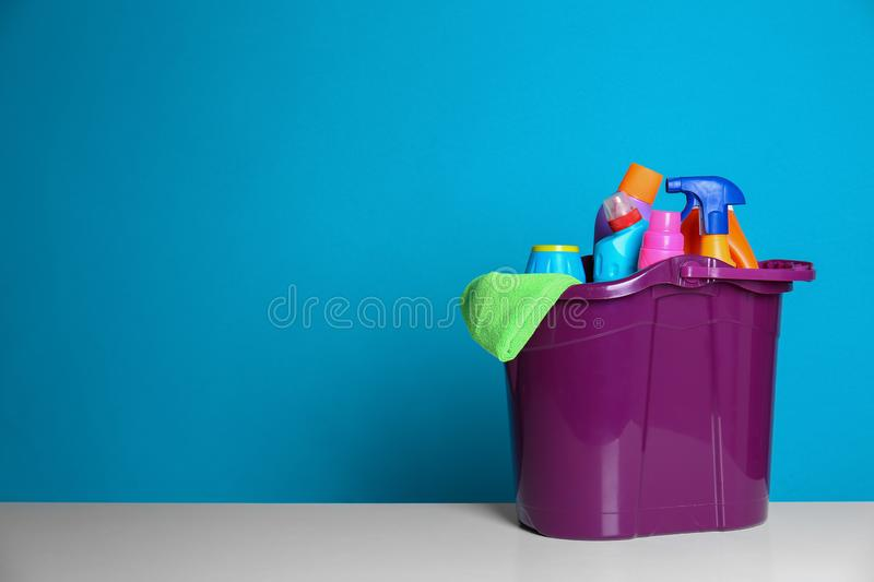 Plastic bucket with different cleaning products on table against color background. Space for royalty free stock photography