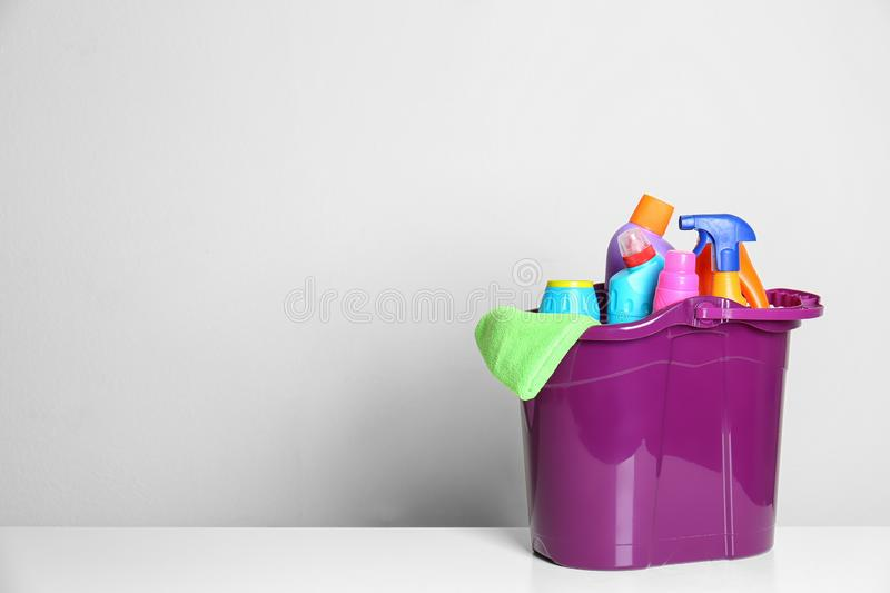 Plastic bucket with different cleaning products on table against light background royalty free stock image