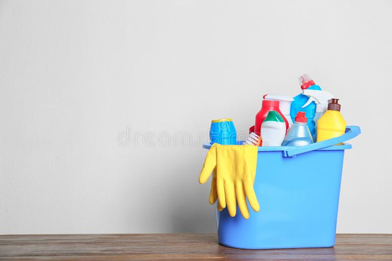 Plastic bucket with different cleaning products on table against light background royalty free stock photos