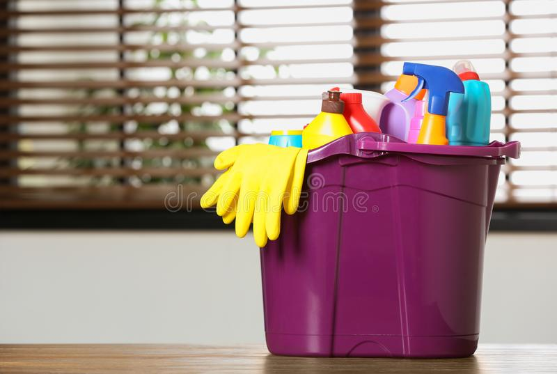 Plastic bucket with different cleaning products on table indoors stock photo
