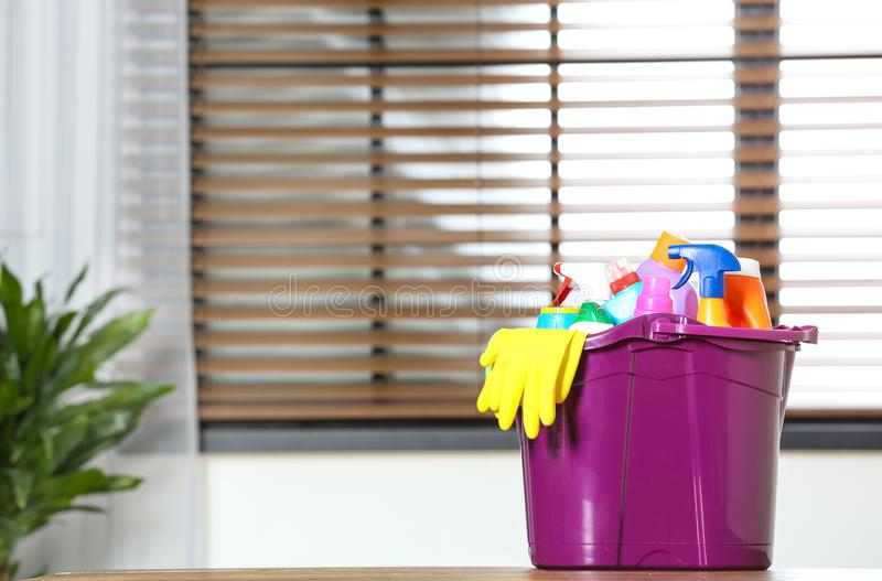 Plastic bucket with different cleaning products on table indoors royalty free stock photos