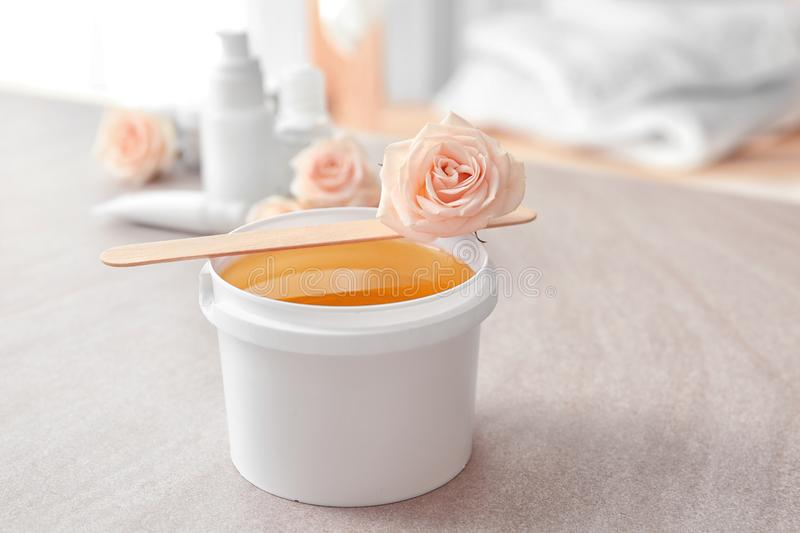 Plastic bucket with sugaring paste, wooden stick stock photography