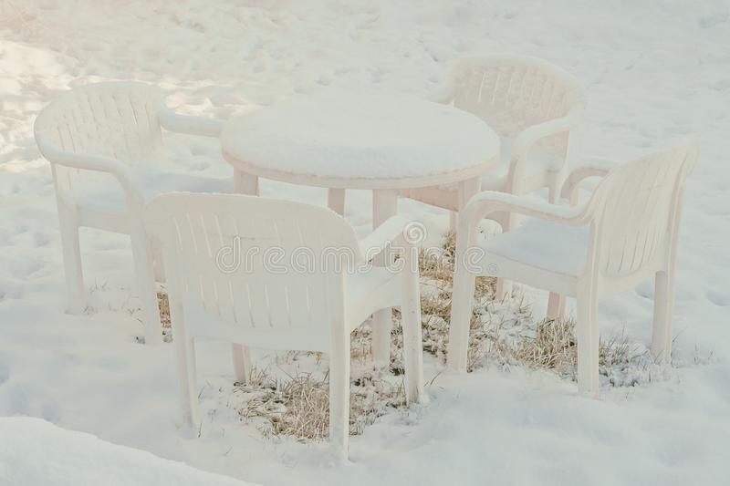 Plastic chairs covered with snow are in the garden. White plastic chairs covered with snow are in the garden royalty free stock images