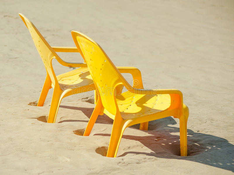 Plastic chairs stands sideways on beach near sea at dawn royalty free stock photography